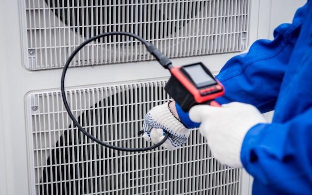 Der techniker überprüft mit einer digitalkamera die verstopfung des wärmetauschers
