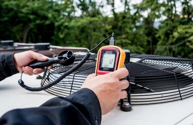 Der techniker verwendet ein handanemometer zur messung des luftstroms, der windgeschwindigkeit und des drucks.