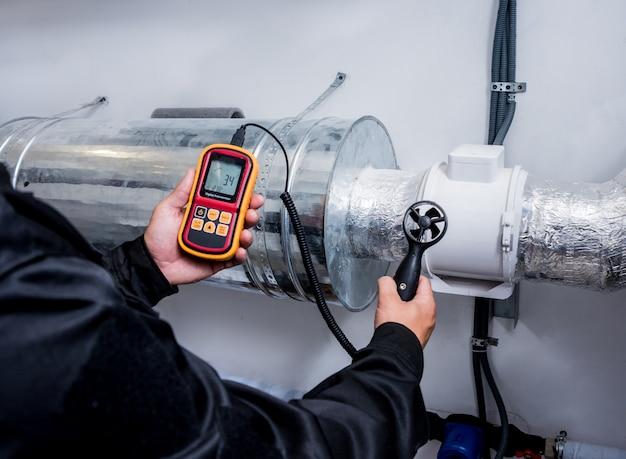 Der techniker verwendet ein handmessgerät, das die messung des luftstroms, die windgeschwindigkeit und den druck misst.
