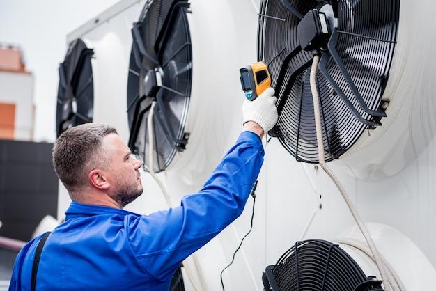 Der techniker verwendet ein wärmebild-infrarot-thermometer, um den wärmetauscher der verflüssigereinheit zu überprüfen