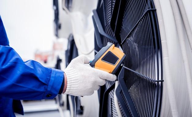 Der techniker verwendet ein wärmebild-infrarot-thermometer, um den wärmetauscher der verflüssigungseinheit zu überprüfen