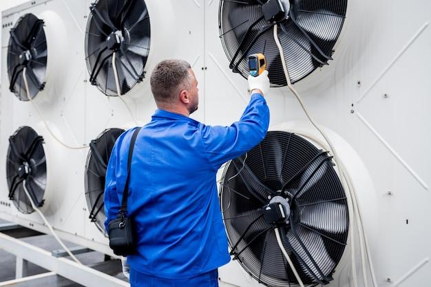 Der techniker verwendet ein wärmebild-infrarot-thermometer, um den wärmetauscher des verflüssigungssatzes zu überprüfen