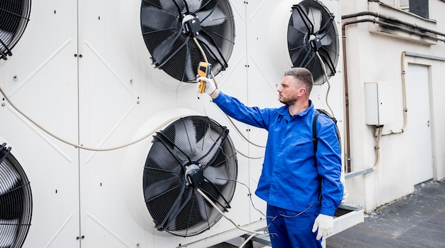 Der techniker verwendet ein wärmebild-infrarot-thermometer, um den wärmetauscher des verflüssigungssatzes zu überprüfen Premium Fotos