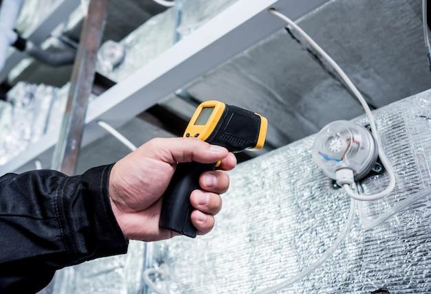 Der techniker verwendet eine infrarot-wärmebildkamera, um die temperatur am sicherungskasten zu überprüfen