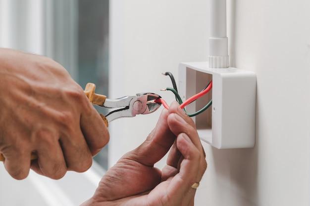 Der techniker verwendet einen zangenschlüssel, um den netzstecker an der wand zu installieren.
