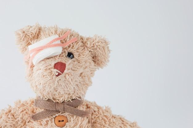 Der teddybär ist verspielt und bekam einen unfall, also wendete er medizinische und verletzte augen mit verband an.