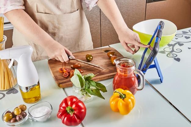 Der teenager gleitet beim kochen durch die virtuelle online-meisterklasse mit dem finger über den tablet-bildschirm, schaut sich digitale rezepte an, während er in der küche zu hause eine gesunde mahlzeit zubereitet