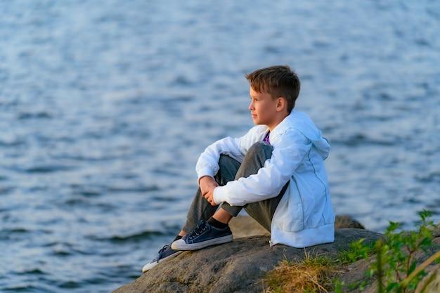 Der teenager sitzt auf einem großen steinbrocken am ufer des flusses und schaut auf den fluss darunter. sommer berufung. hellgrüne vegetation, blauer himmel.
