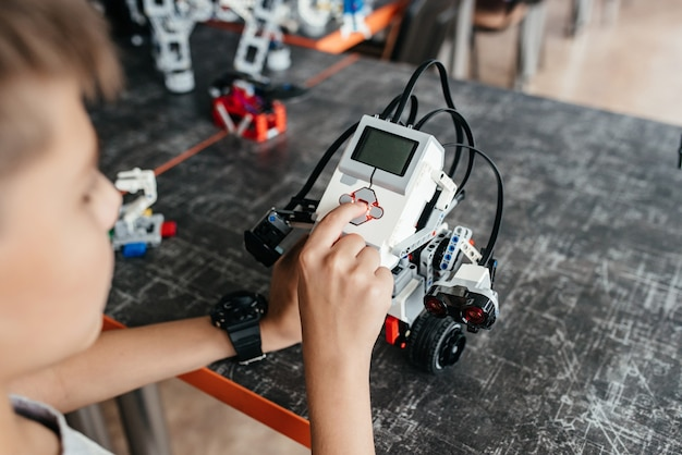 Der teenager spielt mit dem roboter am tisch.