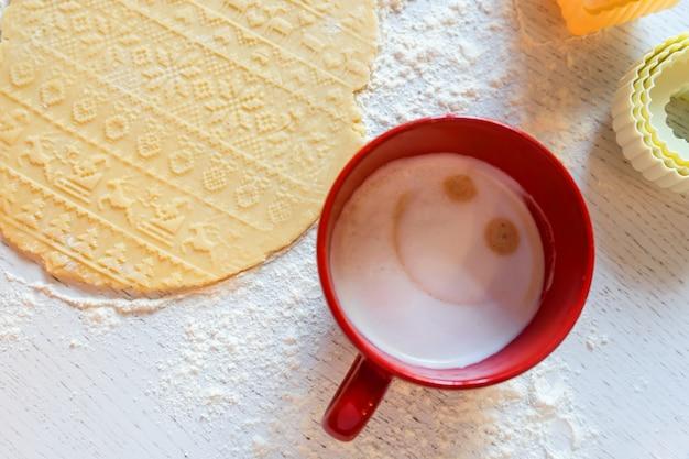 Der teig mit dem neujahrsmuster wird auf dem tisch ausgerollt, daneben stehen ausstechformen und eine rote tasse mit kaffee.