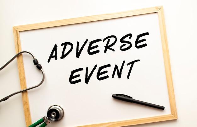 Der text adverse event wird auf eine weiße bürotafel mit einem marker geschrieben. in der nähe befindet sich ein stethoskop