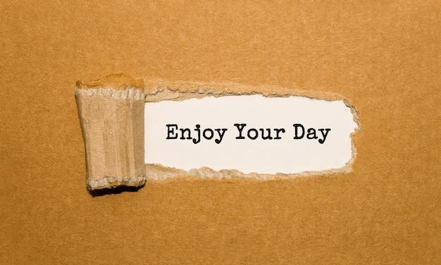 Der text enjoy your day erscheint hinter zerrissenem braunem papier