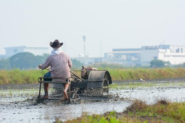 Der thailändische landwirt, der pinne traktor fährt, um reisfeld zu pflügen, bereiten neuen reis vor