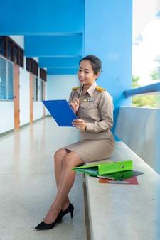 Der thailändische lehrer im offiziellen outfit überprüft den ordner