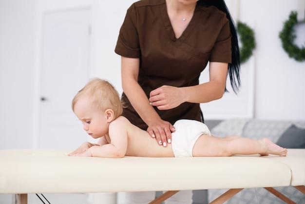 Der therapeut massiert ein kleines baby in einem modernen, gemütlichen zimmer. gesundheitswesen und medizinisches konzept.