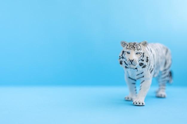 Der tiger, symbol des jahres 2022. kunststoff weiße spielzeugfigur tiger auf blauem grund. platz für text