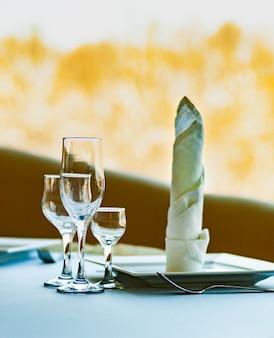 Der tisch in einem café mit geschirr und weingläsern steht an einem sonnigen, wolkenlosen tag vor einem verschwommenen großen fenster mit herrlichem blick auf die winternatur. winterurlaubskonzept