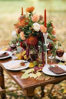 Der tisch mit blumen und kerzen in einem herbstgarten dekoriert