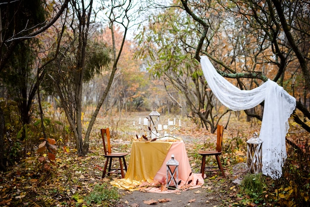 Der tisch mit herbstlichem dekor für zwei personen im wald. herbsthochzeit. hochzeitsdekorationen