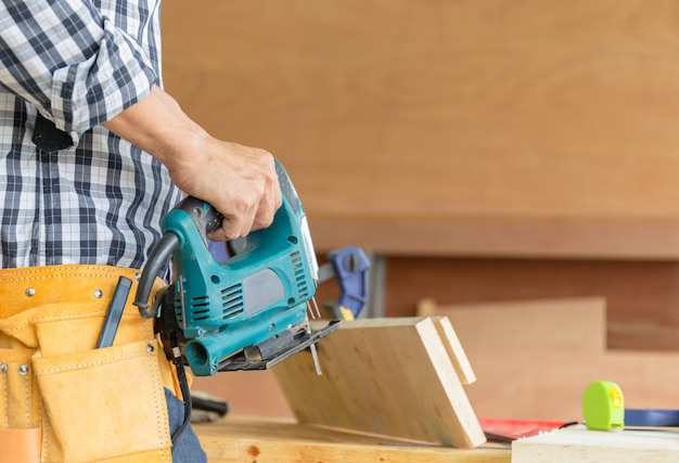 Der tischlermanntischler, der elektrische laubsäge, handwerkerkonzept hält.