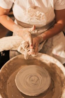 Der töpfer der frau, der nahe der töpferscheibe säubert ihre hände mit serviette sitzt