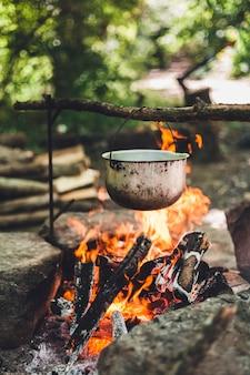 Der topf brennt nachts in der nähe des zeltes im wald. schönes lagerfeuer in einem touristenlager in freier wildbahn.
