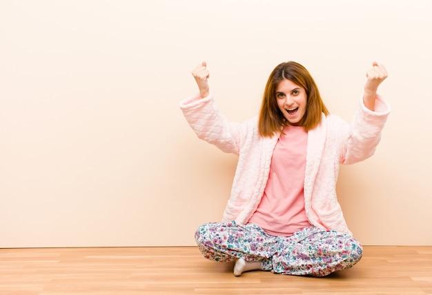 Der tragende pyjama der jungen frau, der zu hause sitzt und einen unglaublichen erfolg feiert, mögen einen sieger und schauen aufgeregt und das glückliche sprichwort nehmen das!