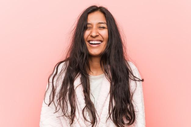 Der tragende pyjama der jungen indischen frau lacht und schließt augen, fühlt sich entspannt und glücklich.