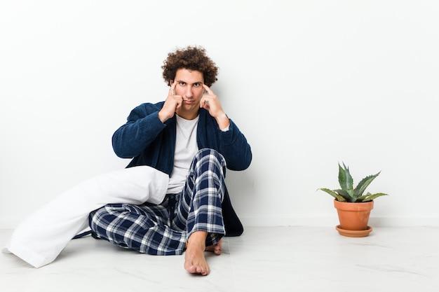 Der tragende pyjama des reifen mannes, der auf hausboden sitzt, konzentrierte sich auf eine aufgabe und hielt die zeigefinger, die kopf zeigen.