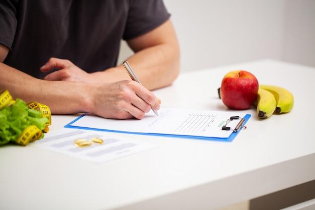 Der trainer erstellt ein trainingsprogramm und einen plan für eine gesunde ernährung