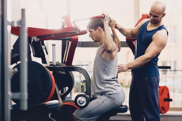 Der trainer kontrolliert die körperliche übung des mannes