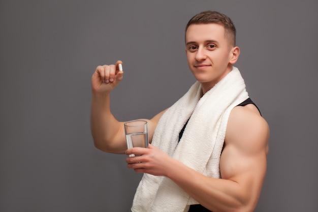 Der trainer nimmt nach dem training eine tablette mit aminosäuren ein