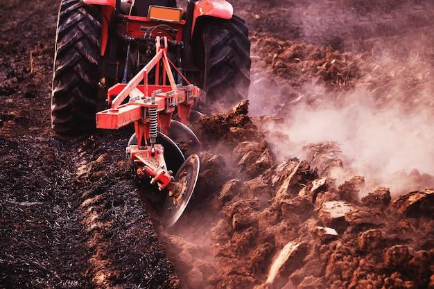 Der traktor bearbeitet den boden und bereitet den boden für die landwirtschaftliche landwirtschaft vor.