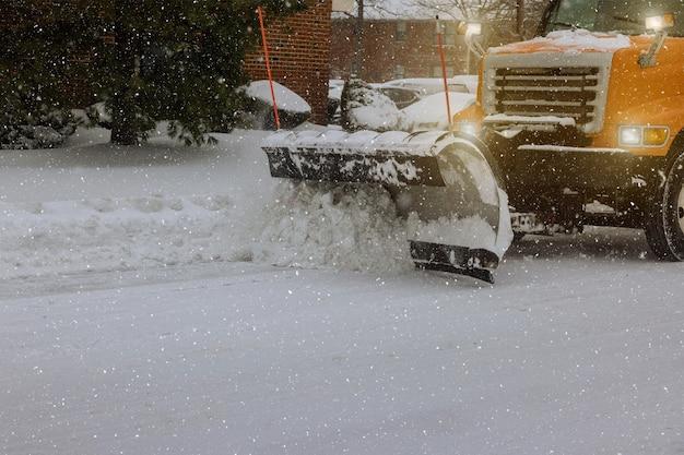 Der traktor räumt die schneeräumung nach dem schneesturm ab