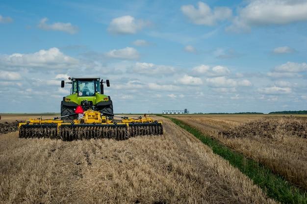 Der traktor zieht einen scheibengrubber, das bodenbearbeitungssystem im feld bereitet sich auf die neue saison vor