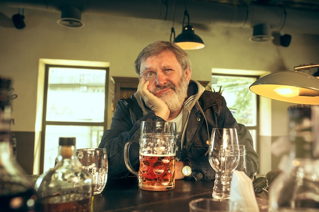 Der traurige ältere bärtige mann, der bier in der kneipe trinkt