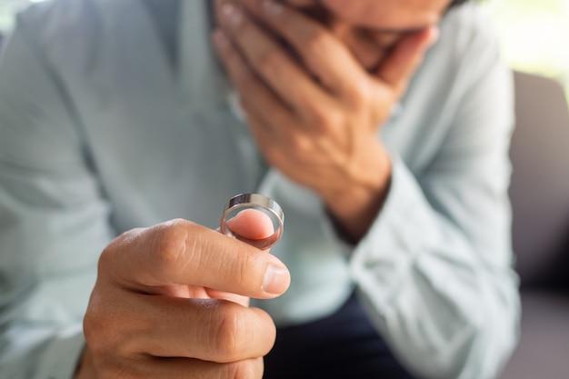Der traurige ehemann hält nach der scheidung den ehering. das ende der familiären probleme
