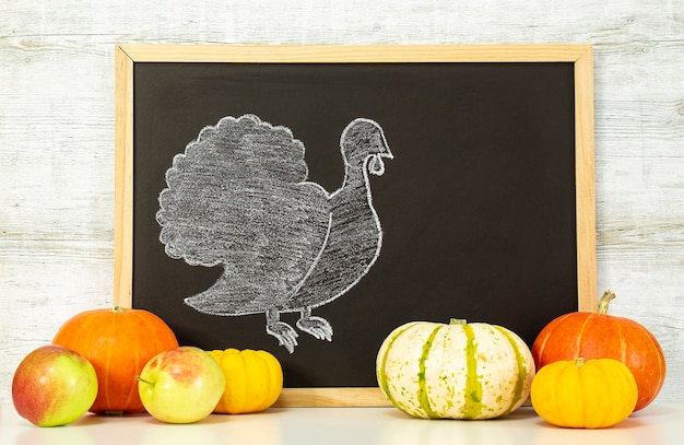 Der truthahn wird auf ein schwarzes brett gezeichnet. frohe thanksgiving-grüße. frohes thanksgiving. herbsternte in einer zeit des überflusses. herzlichen glückwunsch zu den jahreszeiten