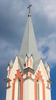 Der turm der katholischen kirche gegen den himmel mit wolken