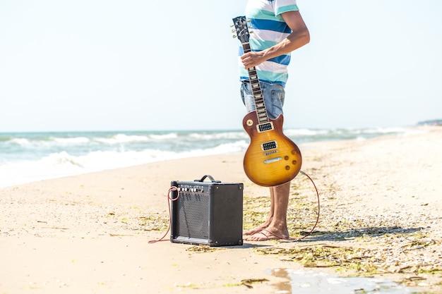 Der typ am strand mit musikinstrumenten