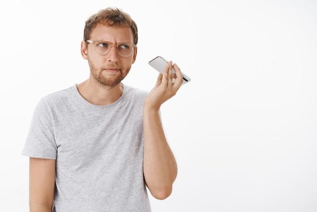 Der typ, der eine audio-nachricht hört, kann nicht verstehen, welches seltsame geräusch von der dynamik kommt, die das smartphone in der nähe des ohrs hält und mit einem intensiven, fokussierten ausdruck, der sich auf den klang konzentriert, beiseite starrt
