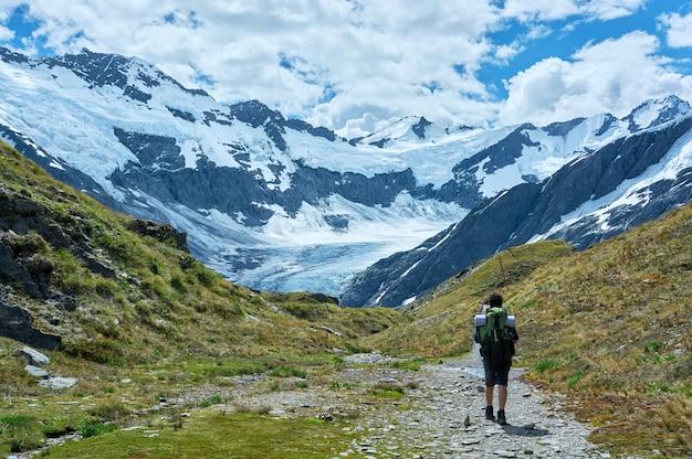 Der typ, der einen rucksack trägt, wandert auf einem gras-tal in richtung eines gletschers und einer bergkette