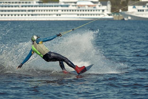 Der typ fährt ein wakeboard auf dem fluss. aktiv- und extremsport.