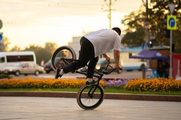 Der typ führt einen stunt auf bmx aus und steht auf dem vorderrad. für jeden zweck.