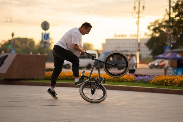 Der typ führt einen stunt auf bmx durch und steht auf dem hinterrad. für jeden zweck.