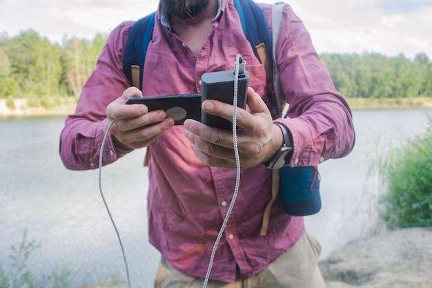 Der typ hält ein tragbares ladegerät mit einem smartphone in der hand. mann auf einem hintergrund der natur mit einem grün und einem see.