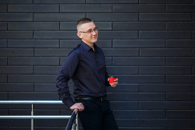 Der typ im schwarzen hemd trinkt kaffee aus einem roten pappbecher.