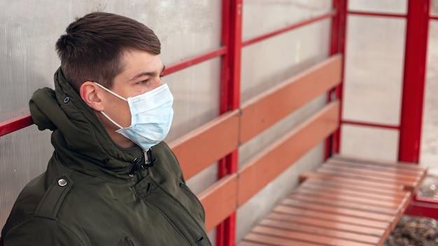 Der typ in der medizinischen maske an der bushaltestelle, coronavirus-pandemie.