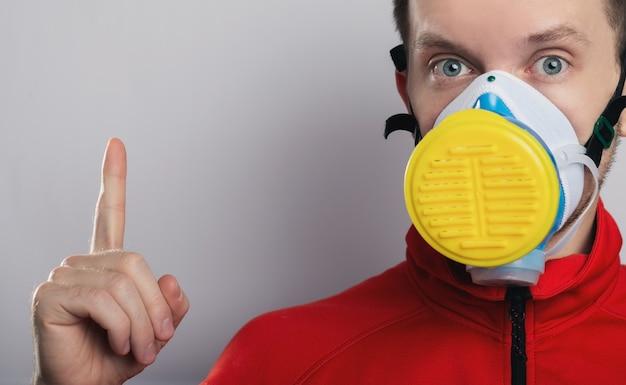 Der typ in der schutzmaske zeigt mit dem finger nach oben.