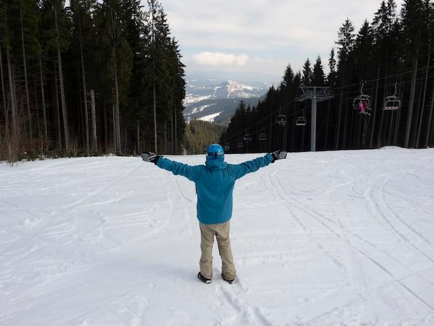 Der typ ist ein snowboarder, der einen blick auf das skigebiet genießt